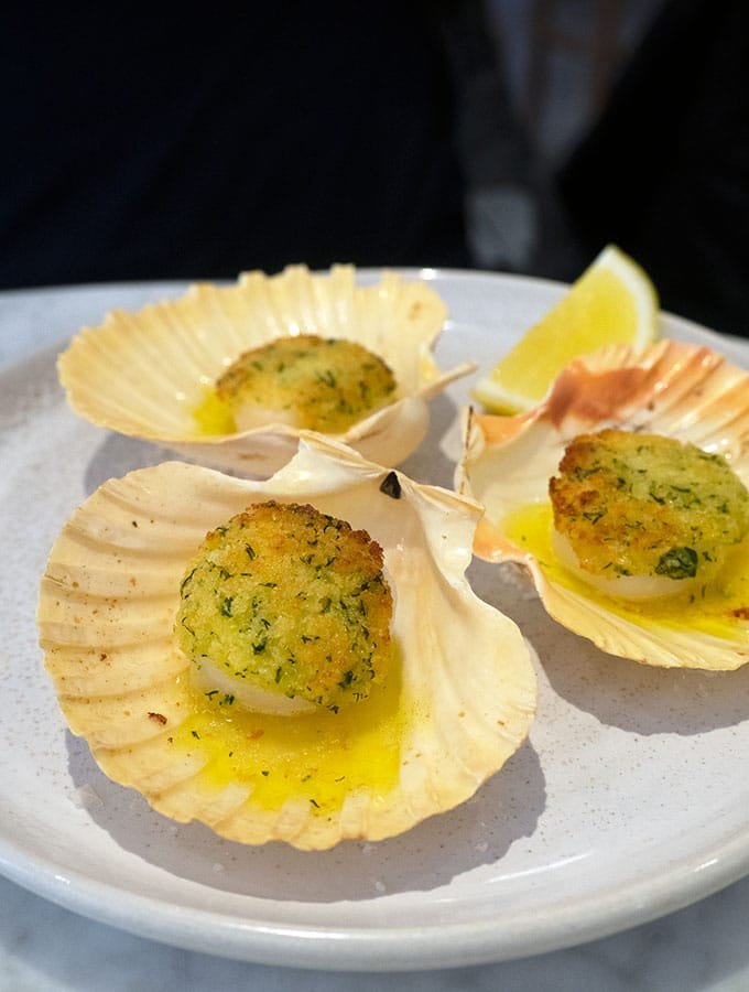 baked sea scallops on the shell served on a plate