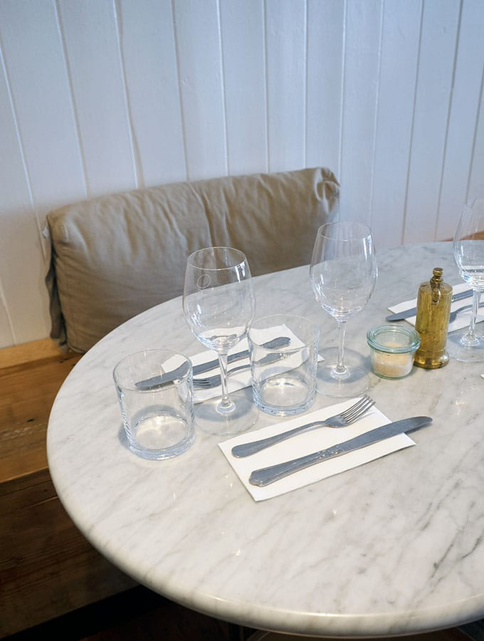 a marble table at queen street eatery set with glasses knives and forks