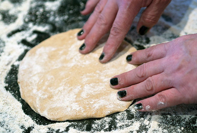 fingers pressing out a circle of spelt dough ready to bake