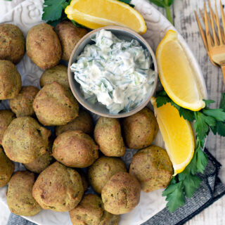 baked falafel on a plate with wedges of lemon
