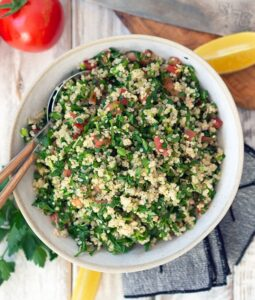 tabouli in a ceramic serving bowl on a table with wedges of lemon