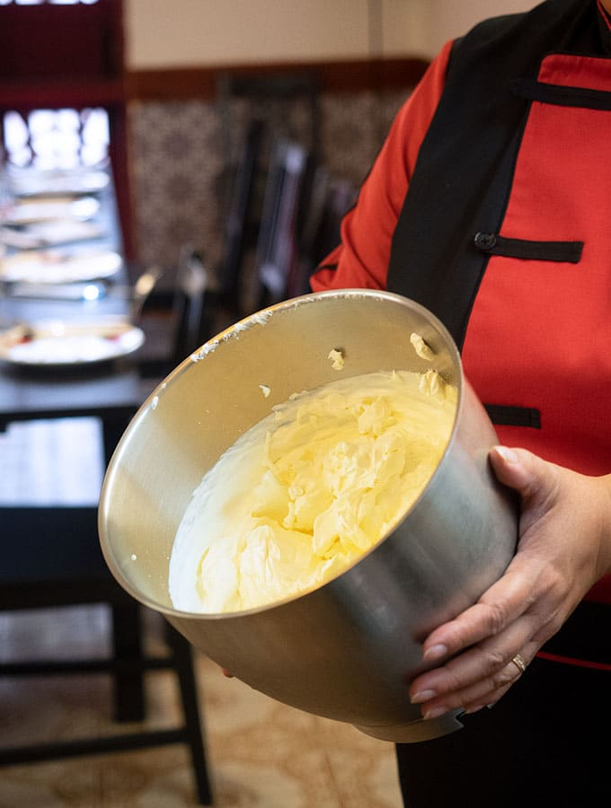 Chef Anna Manhao showing a mixing bowl where cream and condensed milk are being combined