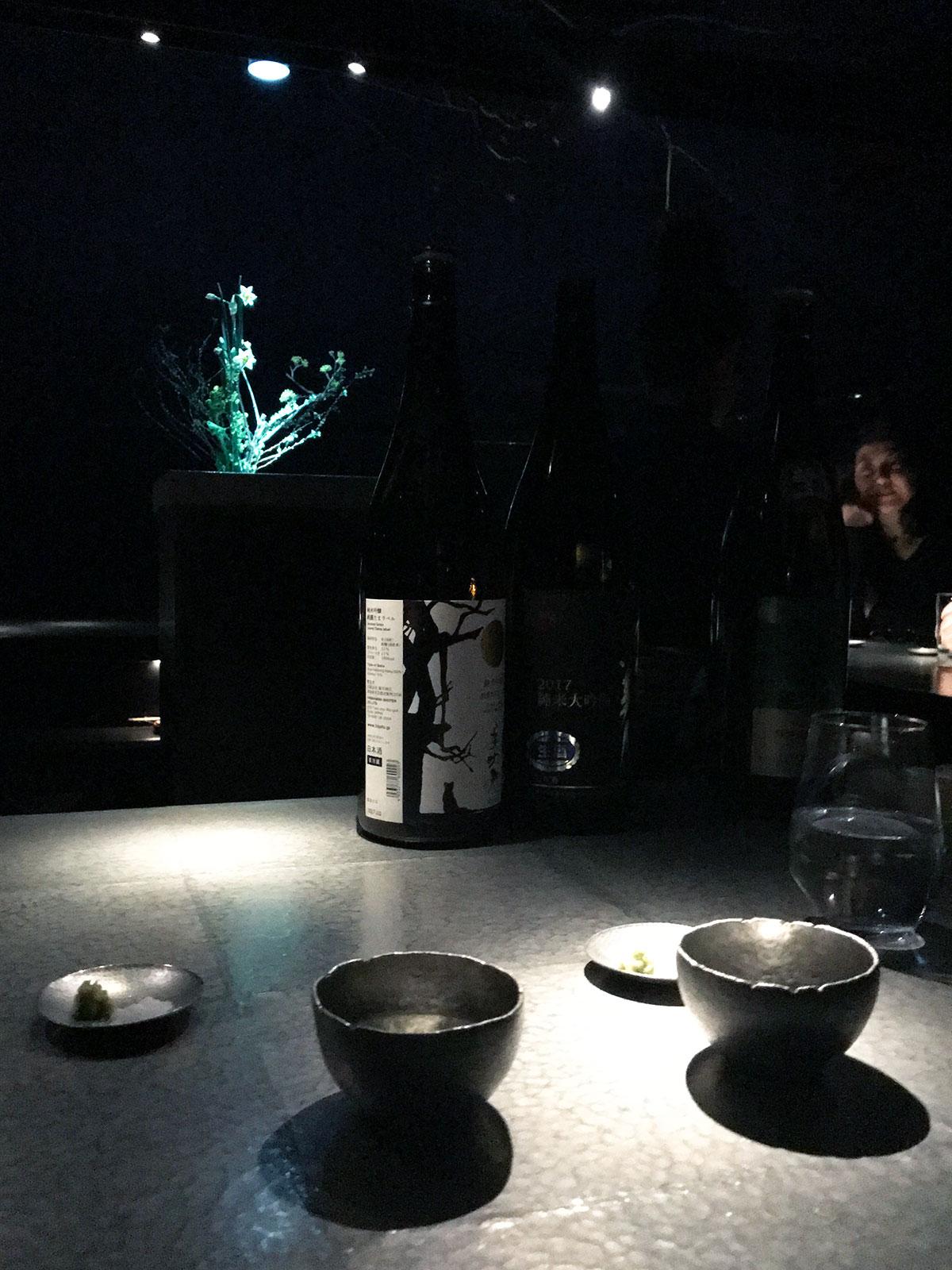 sake cups and bottle on a tin counter at Sake Bar O