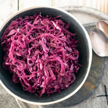 braised red cabbage in a bowl, on a plate with two spoons at the side