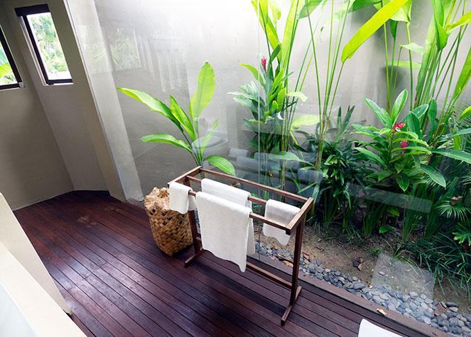 towel rack in cabin bathroom with garden behind