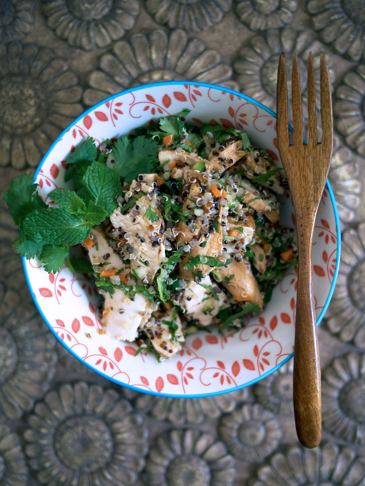 round bowl with chicken quinoa salad and a wooden fork resting on top