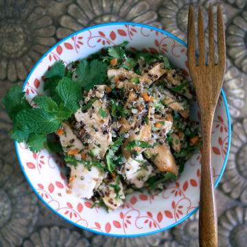 chicken quinoa salad in a round bowl with a wooden fork