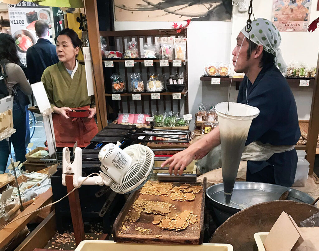 man selling freshly made crackers to customers at nishiki markets