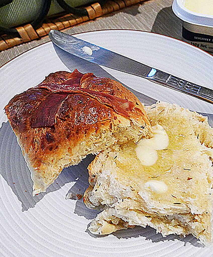 savoury hot cross bun with a prosciutto cross cut in half and slathered with butter on a plate