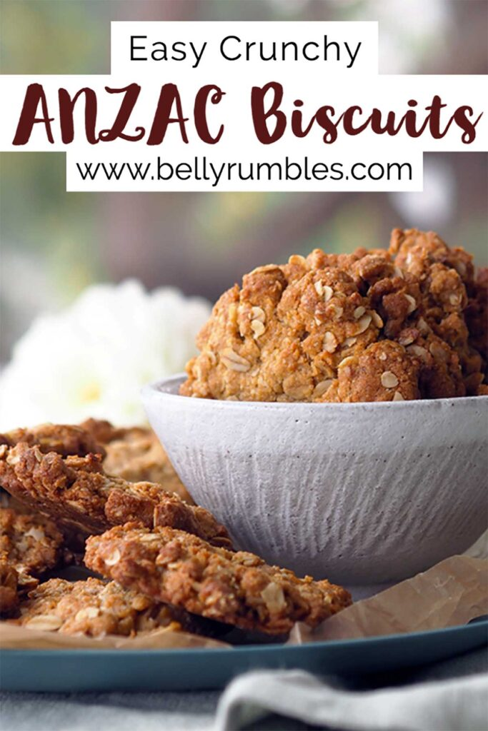 Anzac biscuits in a bowl sitting on a plate with more Anzac biscuits