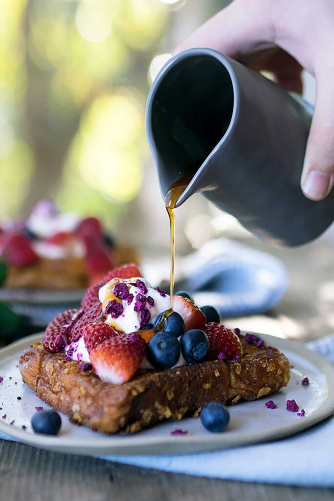 A person pouring maple syrup over french toast toped with berries and yoghurt on a plate
