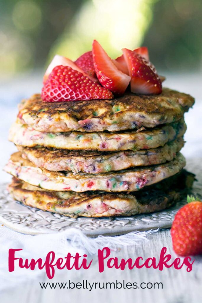 stack of funfetti pancakes topped with fresh strawberries sitting on a white plate