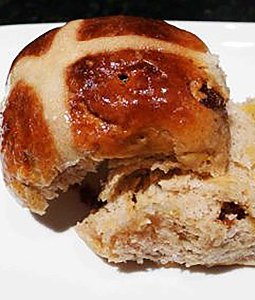 close up of an apricot and fig hot cross bun cut in half on a white plate
