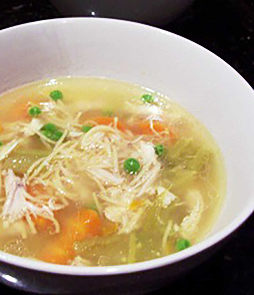 white bowl of chicken soup with thin noodles, carrots, celery and peas