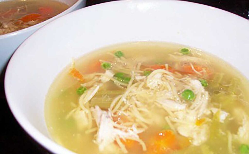 bowl of chicken soup with peas, thin noodles, carrot, chicken pieces and celery