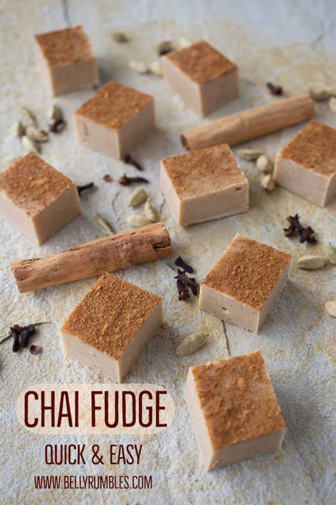 squares of chai fudge on a sandstone tile surrounded by dry spices