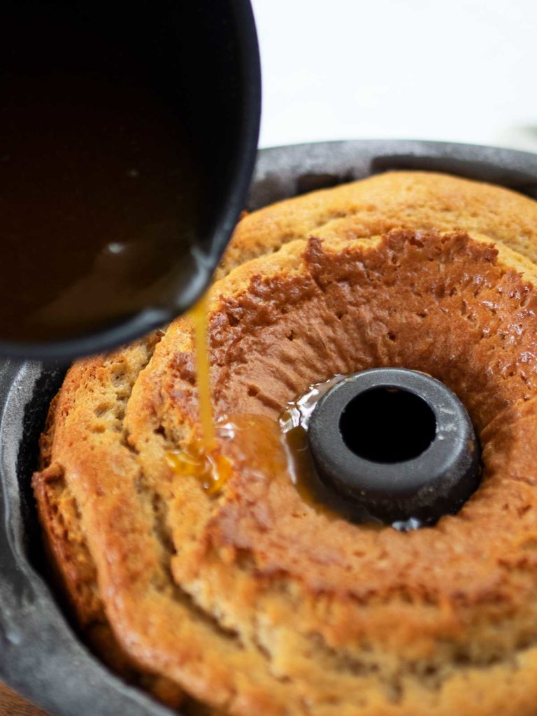 pouring wine sugar syrup over crack cake still in bundt tin