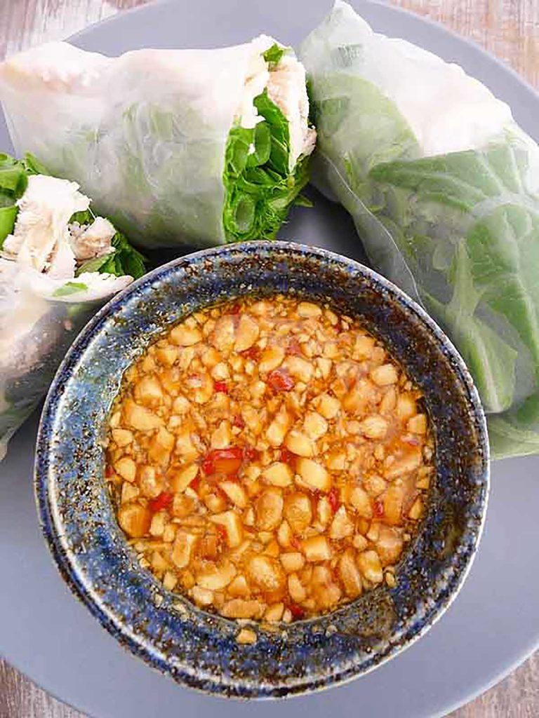 vietnamese sping roll sauce with peanuts and passion fruit in a blue bowl next to fresh spring rolls