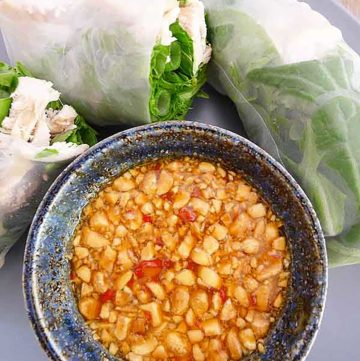 peanut passion fruit dipping sauce in a bowl next to vietnamese fresh spring rolls