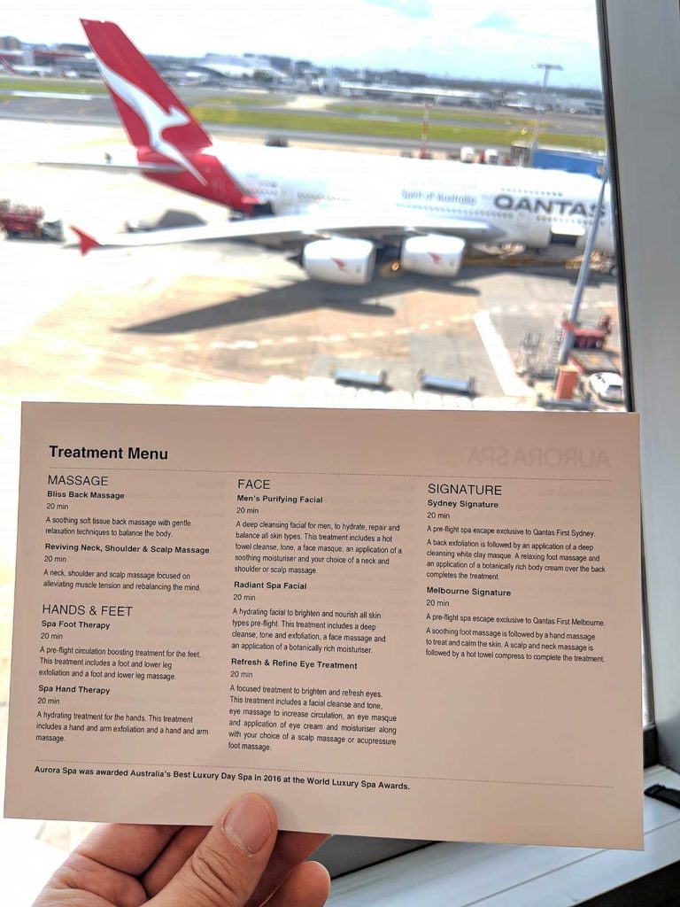 picture of the qantas spa menu taken in front of a window with a plane in the background