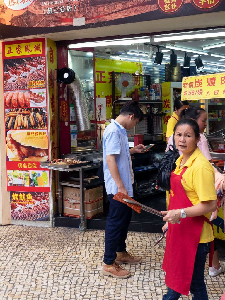 shopkeeper in macao outside of her shop