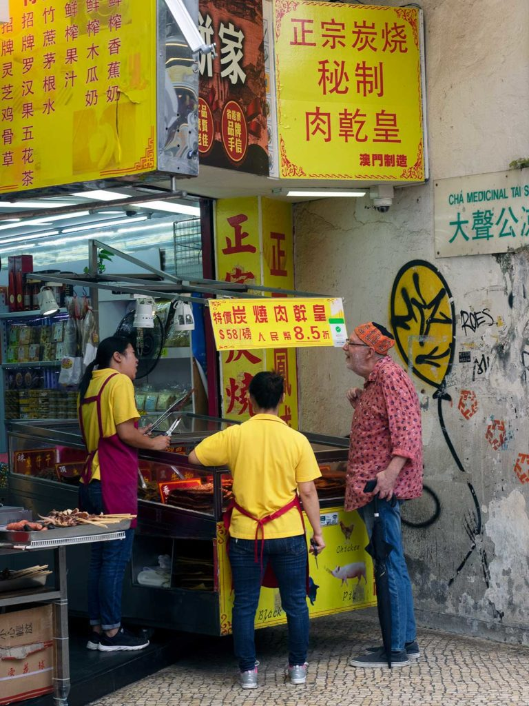 shop owners of a bak kwa shop giving out samples in macao
