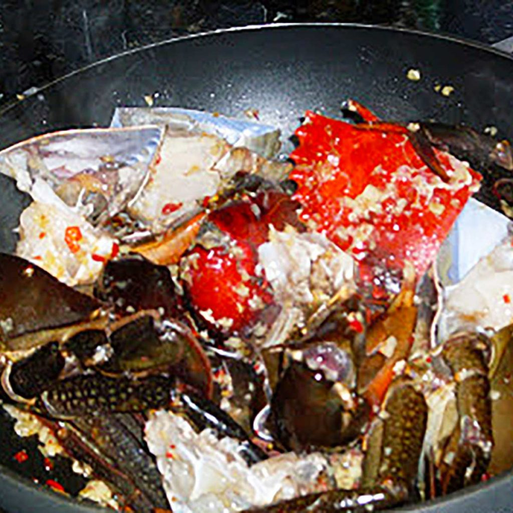 chilli mud crab being tossed in a wok