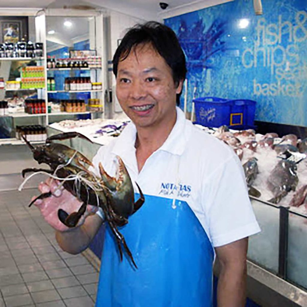 fishmonger in a fish shop holding a live large mud crab