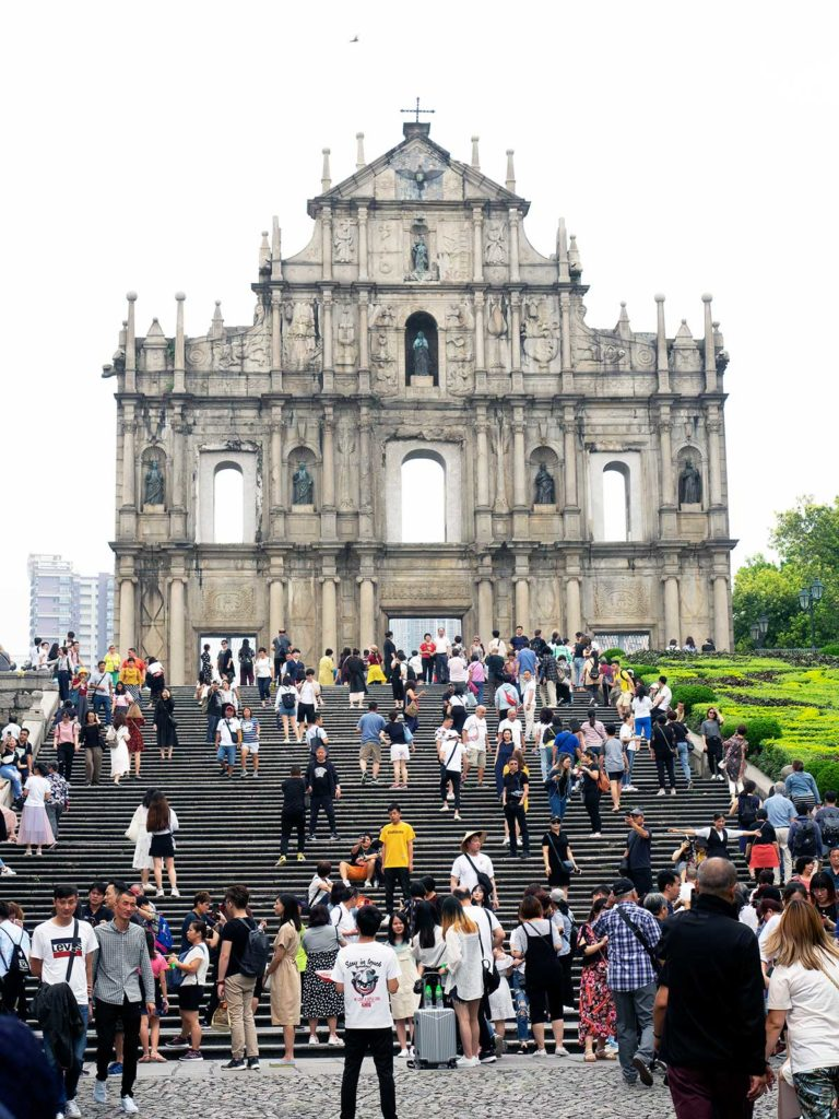 ruins of st paul's in macao with tourists standing in front and on the steps