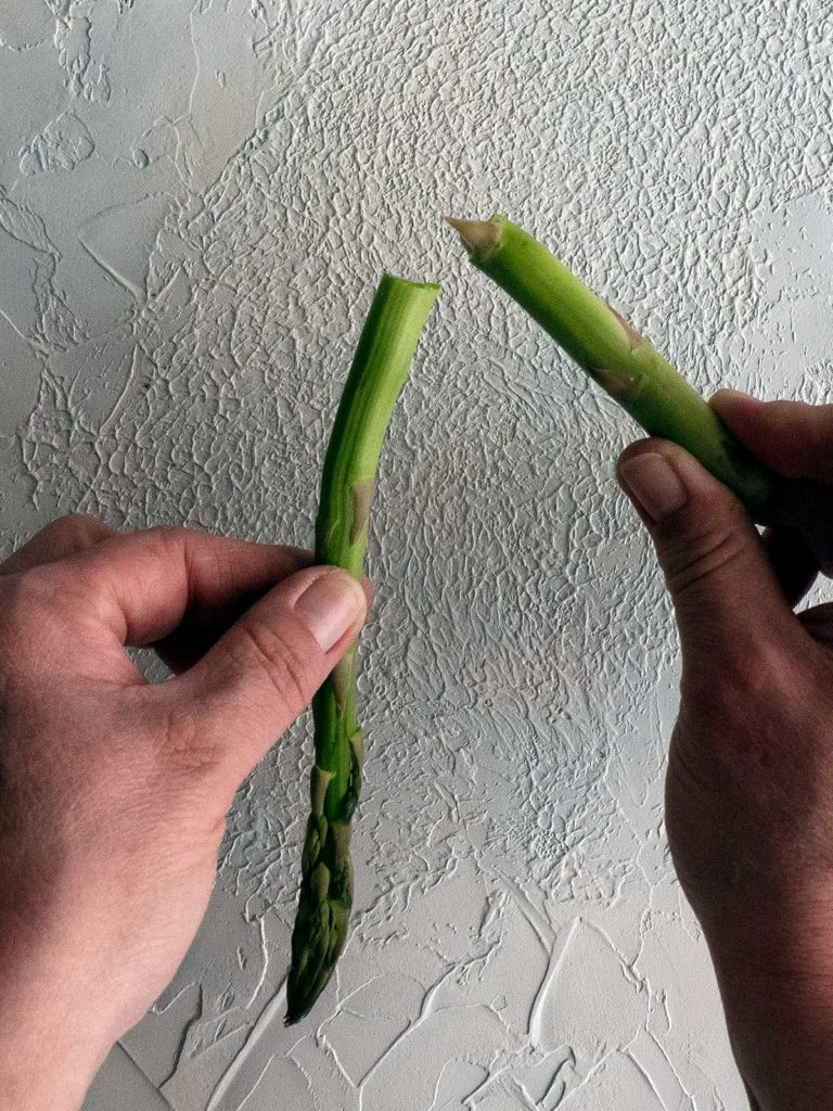 asparagus being snapped to remove the woody end