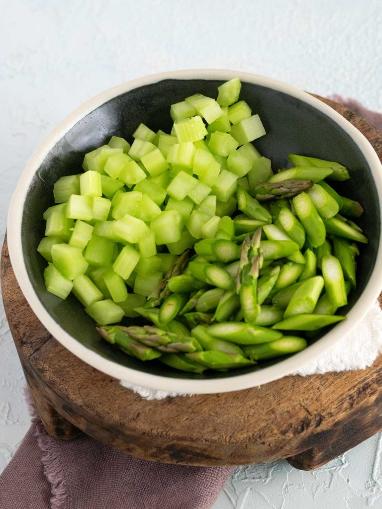 diced asparagus and celery in a black bowl