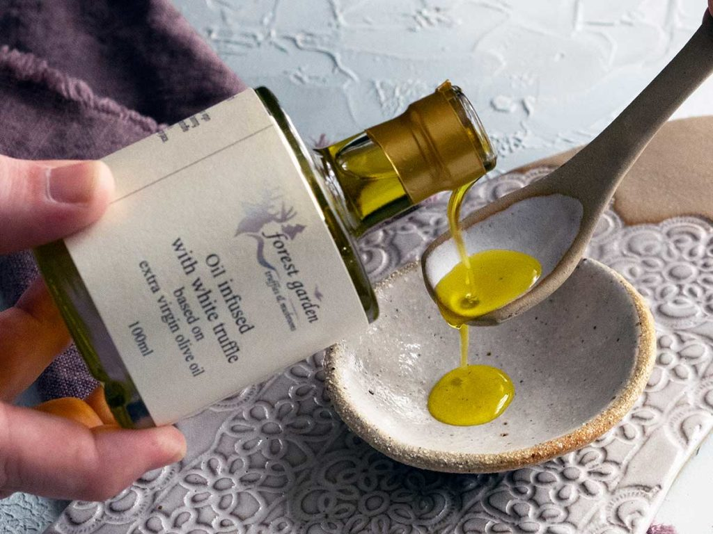 grecian purveyor white truffle oil being poured on to a ceramic spoon