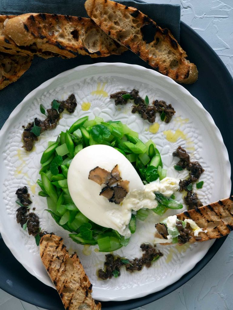 burrata on a bed of asparagus and celery, topped with truffle carpaccio, salsa tartufata dolloped around the outside on a white plate. grilled bread being used to eat it