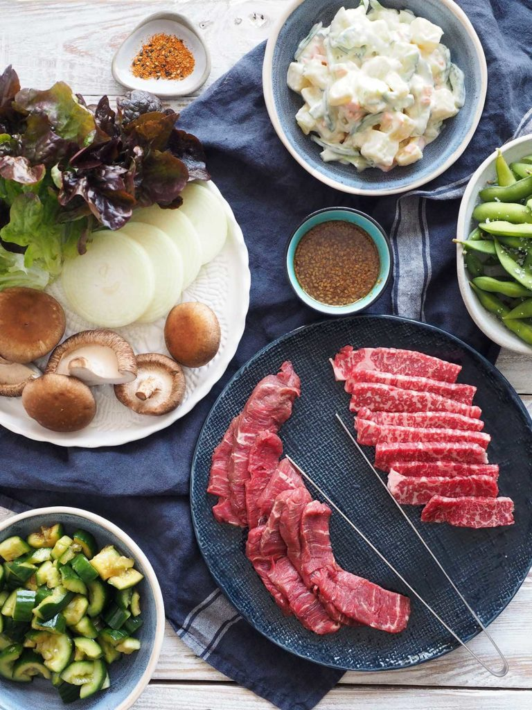 Ingredients for Yakiniku, beef slices on a plate, crushed cucmbers in a bowl, slices of onion, whole shitake mushrooms and lettuce on a plate, sauce in a bowl, cooked edamame in a bowl and Japanese potato salad in a bowl