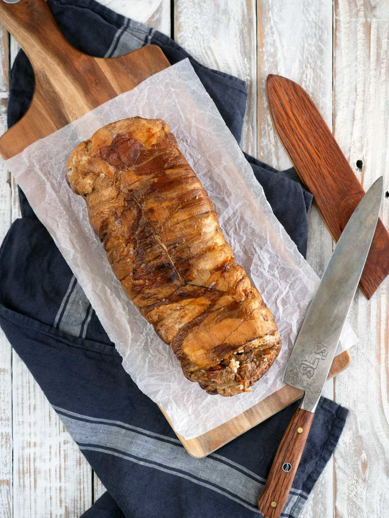 whole piece of chashu on a cutting board ready for slicing