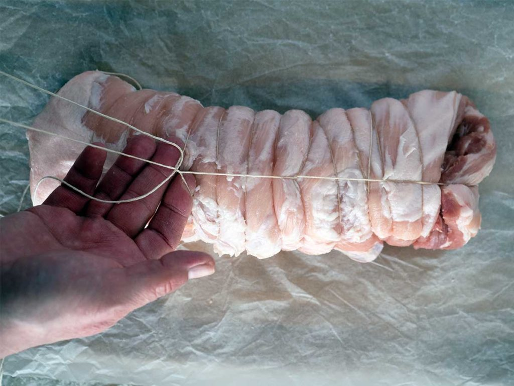 tying a rolled piece of pork belly with string