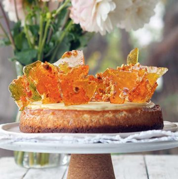 Cheesecake topped with shards of toffee, place on top of a cake stand, flowers and greenery adorn the background