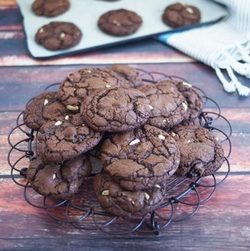 dark chocolate coockies resting on a black rack, dark wood background