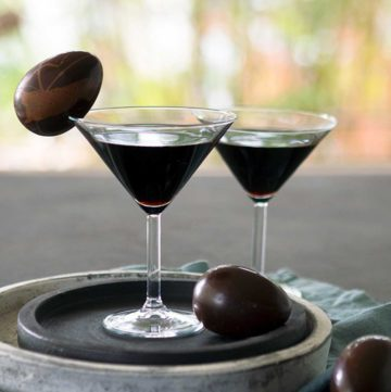 Dark almost black cocktail in a martini glass garnished with a dark chocolate egg on the rim