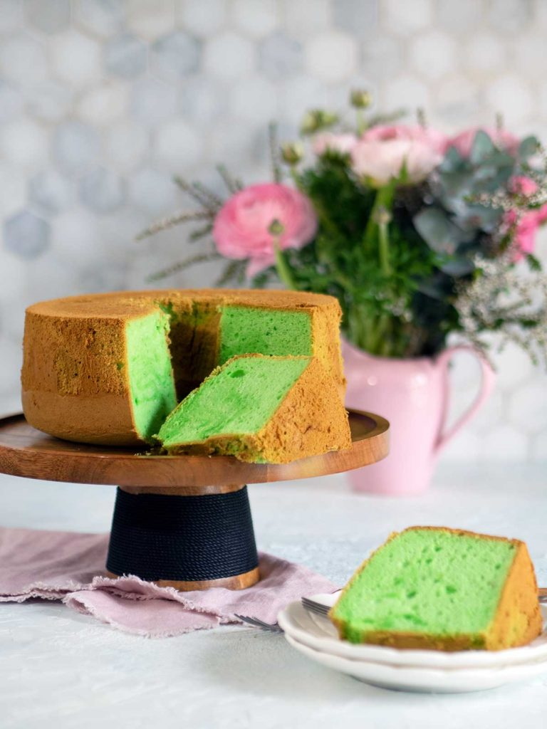 pandan cake on wooden cake stand with slices removed