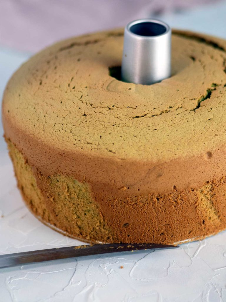 knife being inserted between bottom of cake and base of tin to remove cake from tin