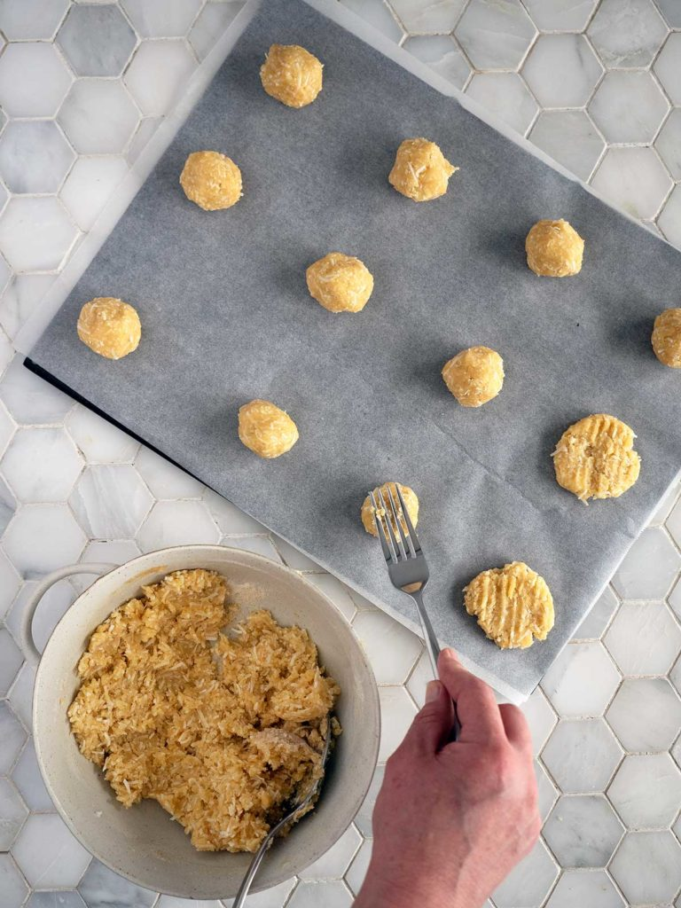 cookie dough balls on a baking sheet being flattened by a fork