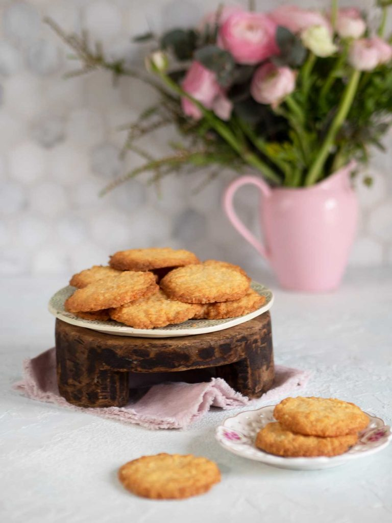 coconut cookies on a plate on a wooden stand, some more cookies in front and vase with pink flowers behind