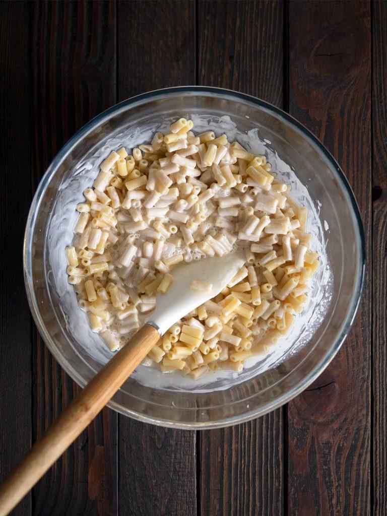 cream mixture being mixed into macaroni