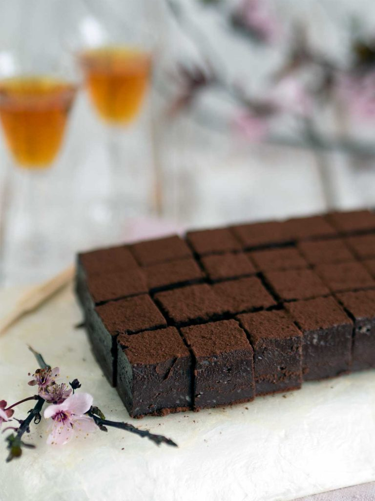 squares of nama chocolate on a tray with a sprig of cherry blossom front lefthand side