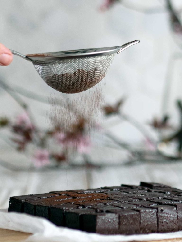 cocoa powder in a sieve being dusted over cut nama chocolate
