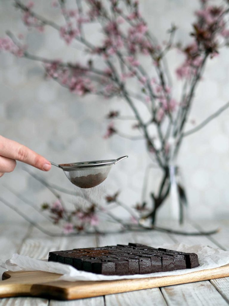 cocoa powder being sifted over the top of cut nama chocolate with cherry blossoms in the background
