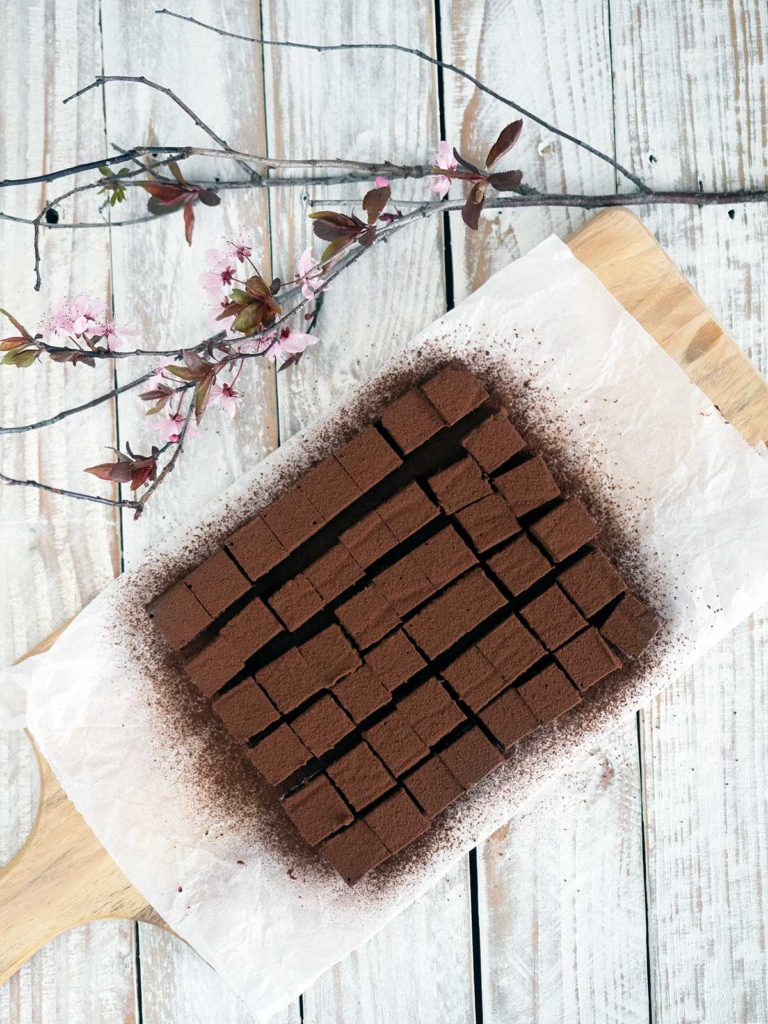 nama chocolate cut into squares dusted with cocoa powder on some paper on a wooden board with cherry blossoms in the top left hand corner