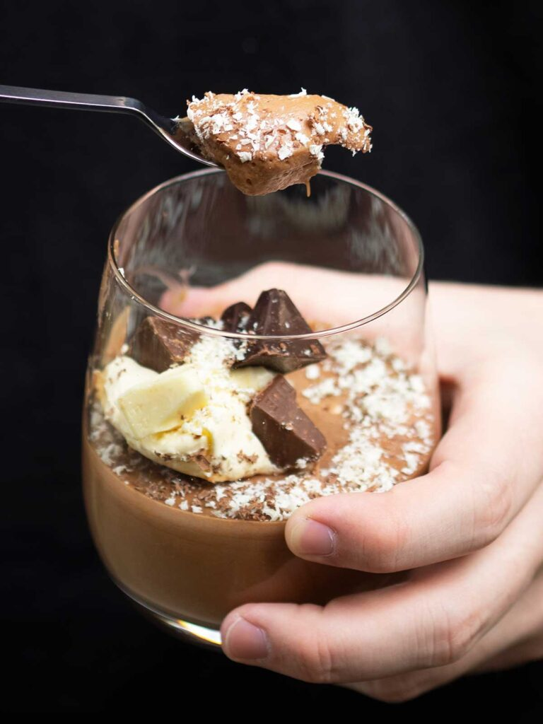 hand holding a glass of Toblerone mousse scooping out a spoonful with the other hand.