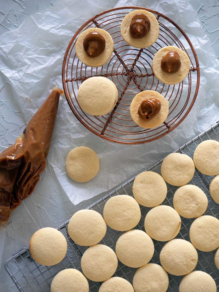 shortbread cookies on racks with piping bag full of dulce de leche, some of the cookies have had dulce de leche piped on to them